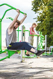 Active man and woman exercising at outdoor gym. Stock Image