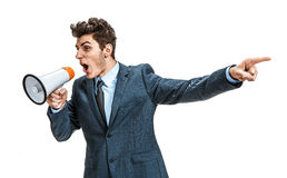 Active manager shouting into a megaphone and finger pointing. Photos of young businessman wearing  a suit and tie over white background Stock Photos