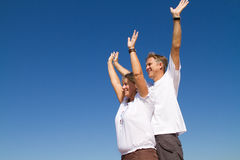 Active mature couple. Happy active mature couple on blue sky Royalty Free Stock Images