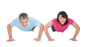 Active mature couple doing pushups Royalty Free Stock Images