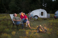 An Active Mature Couple. Sits around a campfire with bicycles and teardrop camper in background Royalty Free Stock Photography