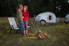 An Active Mature Couple. Sits around a campfire with bicycles and teardrop camper in background Royalty Free Stock Photo