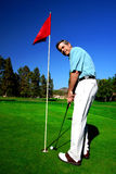 Active Mature Man Golfer. Beautiful green golf course, a red flag and deep blue sky is the setting with an active and fit mature man golfer smiling and ready to Royalty Free Stock Image