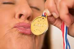 Active Mature woman kissing medal award Royalty Free Stock Photo