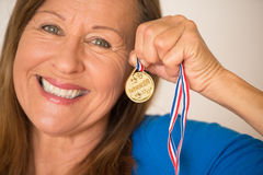 Active mature woman with medal Royalty Free Stock Images
