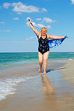 Active mature woman running the beach Stock Images