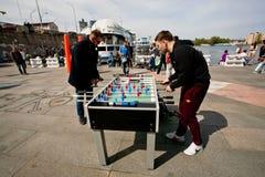 Active men have fun during foosball game Stock Image