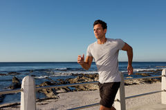 Active middle age man jogging outside by sea. Portrait of active middle age man jogging outside by sea royalty free stock photography