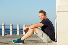 Active middle age man sitting outside and smiling. Side portrait of active middle age man sitting outside and smiling royalty free stock image