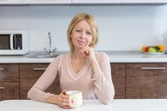 An active middle age woman drinking coffee at home royalty free stock photos