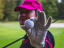 Golf game. A white textured leather golf glove and golf ball close up, selective focus,  blurred background