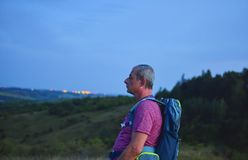 Active middle aged man standing on hill with backpack, enjoy looking at mountains landscape during twilight stock image
