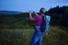 Active middle aged man standing on hill with backpack, taking picture of mountains landscape during twilight. Man taking picture stock photos