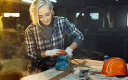 Active Middle aged woman selects wood in workshop. Concept of professionally oriented motivated modern woman. Gender equality, royalty free stock images