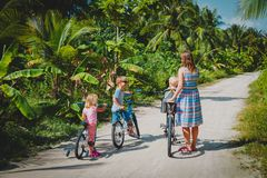Active mom with kids riding bikes on tropical vacation stock photography