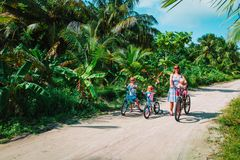 Active mom with kids riding bikes on tropical vacation stock images