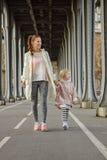 Active mother and child on Pont de Bir-Hakeim bridge walking Royalty Free Stock Images
