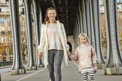 Active mother and child on Pont de Bir-Hakeim bridge walking Stock Photo