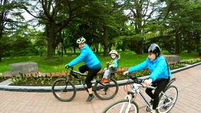 Active Mother With Children Cycling In Green Park stock video