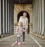 Active mother and daughter standing on Pont de Bir-Hakeim bridge Stock Photo
