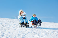 Active mother and kids. Sleighing down the snowy hill Royalty Free Stock Photography