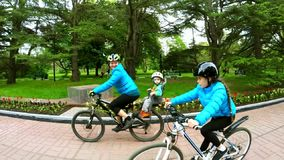 Active Mother With Two Children Cycling In Green stock video footage
