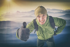 Active mountaniring. Instagram stylisation. Smiling active hiker man with backpack showing thumbs up, everything is OK and good. Sunrise in a misty valley Royalty Free Stock Photo