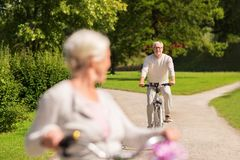 Happy senior couple riding bicycles at summer park Stock Image