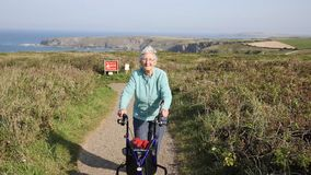 Active old lady pensioner walking towards camera with three wheel trolley mobility aid on coast path stock footage