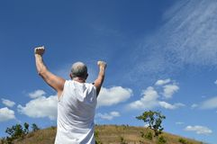 Active older man with arms up in sign of success or achievement on the hill. Stock Image