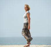 Active older woman walking at the beach. Portrait of an active older woman walking at the beach Royalty Free Stock Images