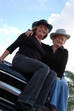 Active older women. Smiling mature woman in jeans and cowboy hats sitting on the hood of a truck Stock Image