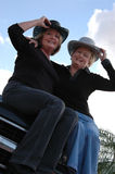 Active older women. Smiling mature woman in jeans and cowboy hats sitting on the hood of a truck Stock Images