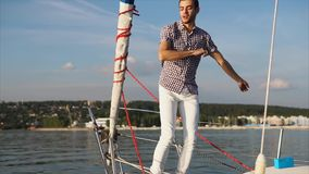 A young and active man dances on a yacht that follows the sea in the daytime stock video