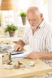 Active pensioner doing financial work at home. Using calculator, looking at bills Royalty Free Stock Images