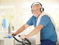 Active pensioner doing spinning with music. Active pensioner doing spinning on bike at home while listening to music, smiling at camera stock images