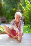 Active pensioner. Fit active pensioner stretching, touching toes royalty free stock photos