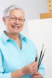 Active pensioner with paintbrush and canvas Stock Images