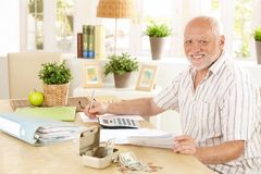 Active pensioner working at home. Taking notes, sitting at table, smiling at camera Royalty Free Stock Photos