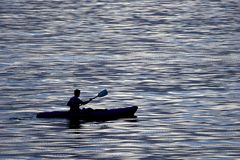 Active people - kayaking. Single male kayaking in blue water Royalty Free Stock Images