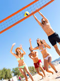 Active people playing ball on beach. Happy smiling adults playing with a ball on a beach. Man jumping to catch a volley ball stock images