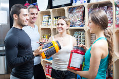 Active people with sport nutrition. Portrait of active people with sport nutrition products in shop Stock Photos