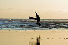 Active Person by the Ocean. An excited person is jumping near the beach Stock Image