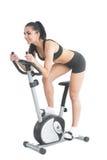Active ponytailed Frauentraining auf einem Hometrainer Stockbilder