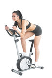 Active ponytailed woman training on an exercise bike Stock Images