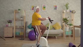 Active positive grandmother in headphones listening to music and engaged on a stationary bike. Active positive retired woman in headphones listening to music and stock video