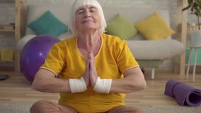 Active positive older woman doing yoga on the carpet in the living room close up. Active positive older woman pensioner doing yoga on the carpet in the living stock footage