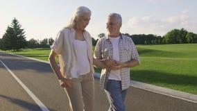 Active positive seniors enjoying a walk in park stock video footage