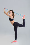 Active positive young fitness woman stretching with jumping rope Stock Photography