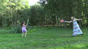 Active pregnant woman with girl play badminton game in park Stock Photo
